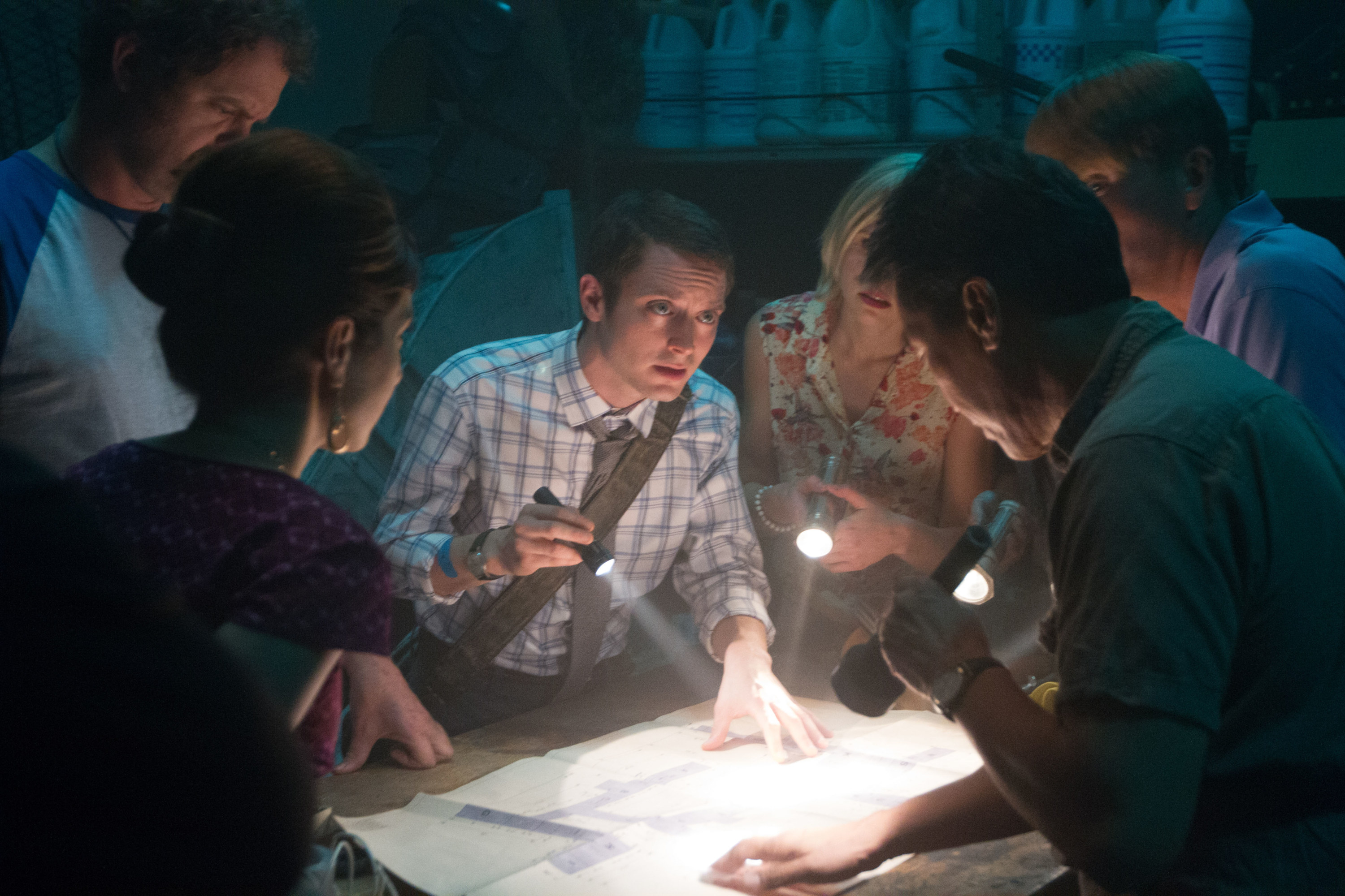 Elijah Wood looking at a large document on a table surrounded by people with flashlights