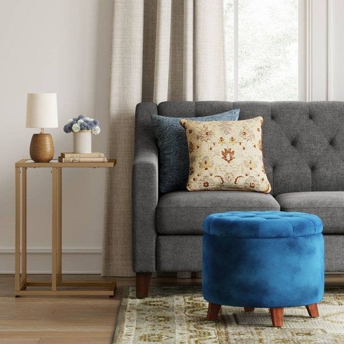 The velvet navy Threshold Tufted Round Storage Ottoman in a living room