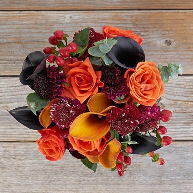 A fall-inspired orange and dark purple bouquet