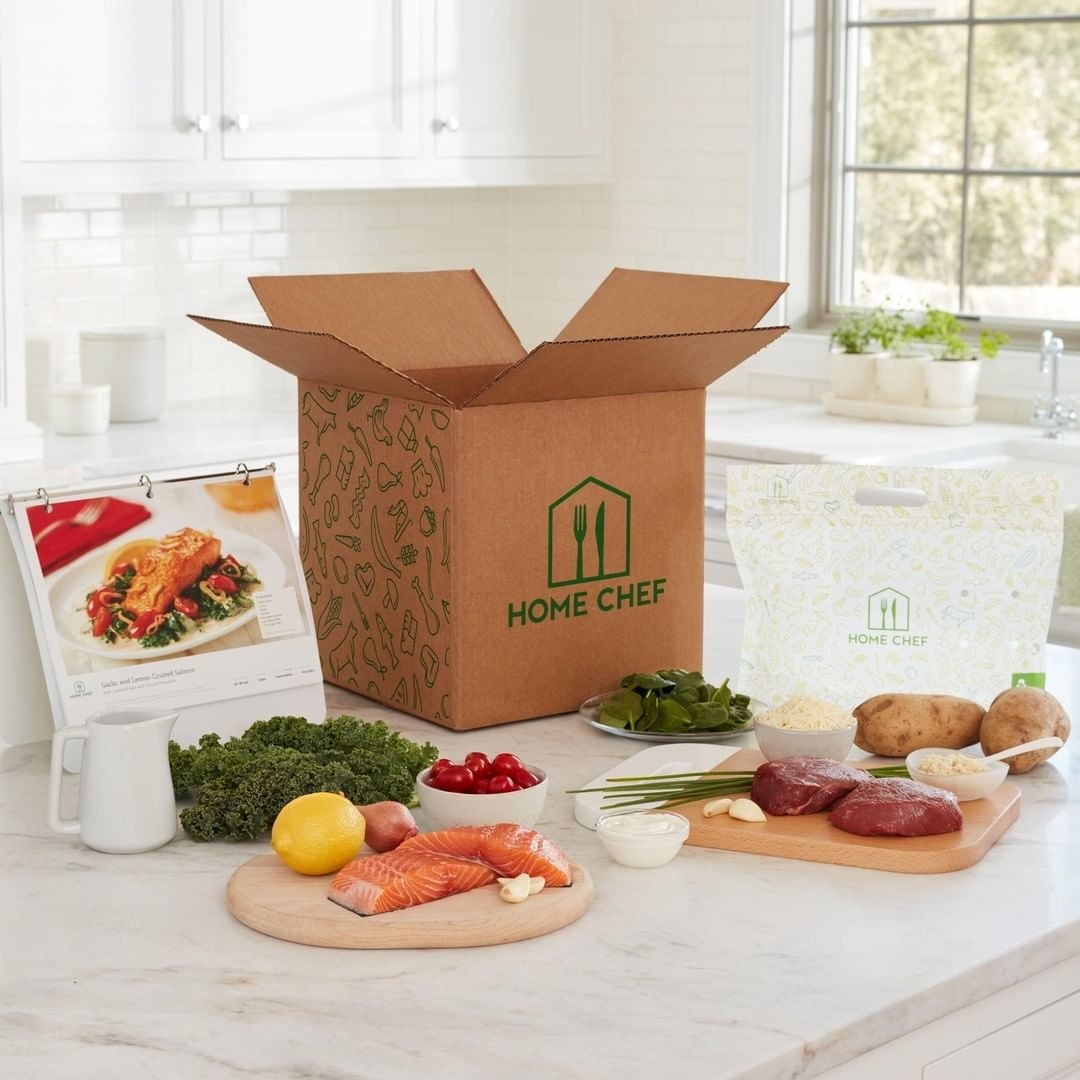 A Home Chef box with all the ingredients to make a meal of salmon and greens and steak and potatoes set out on a counter with the instructions next to it.