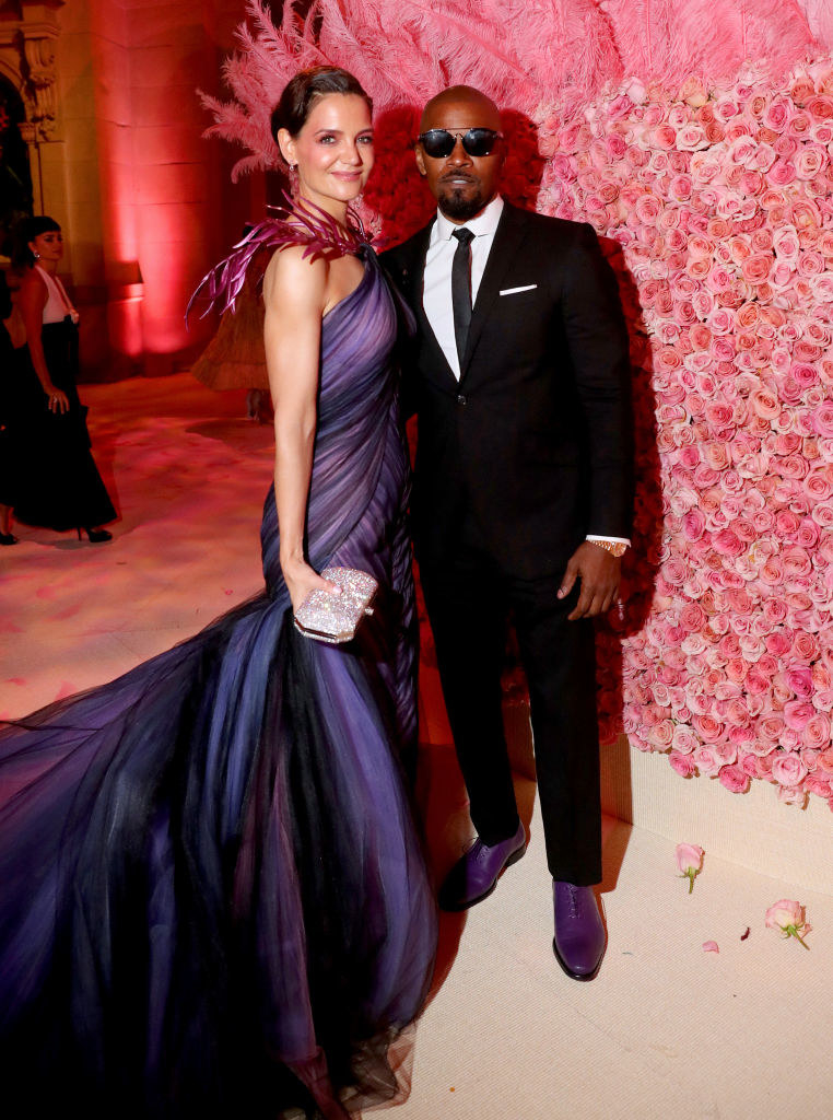 Katie Holmes wearing a poofy dress and Jamie Foxx in a dark suit at an event