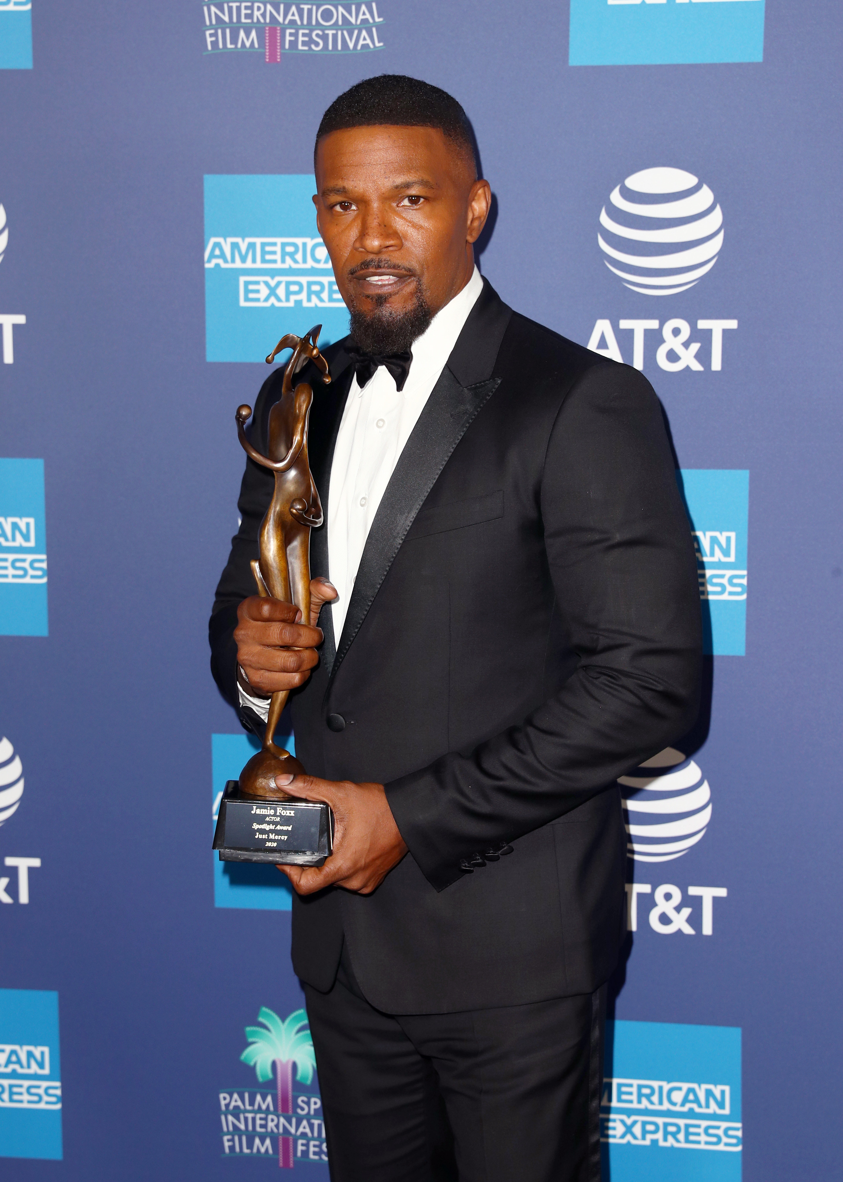Jamie Foxx holding an award wearing a dark suit and bright shirt