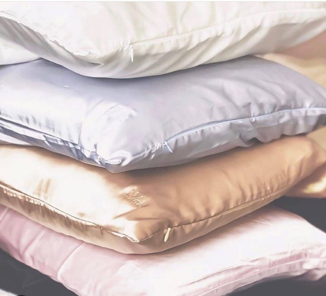 Four pillows with silk pillowcases sitting on top of each other in white, grey, gold, and pink.
