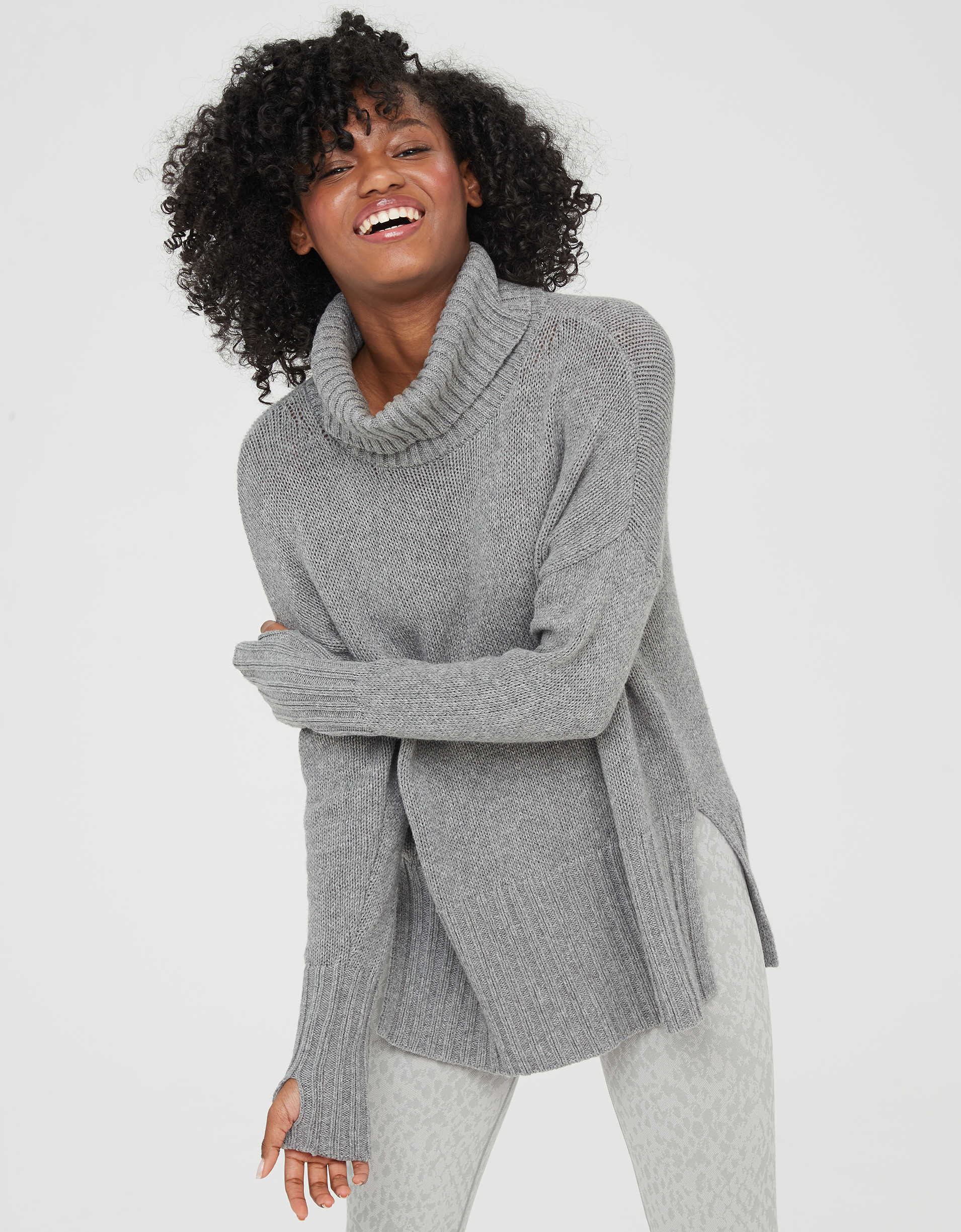 Model wearing the oversized turtleneck in grey with slits on the side and thumbholes on the sleeves.