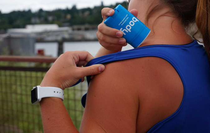 Model holds blue container of body glide anti-chafe balm to soothe chafing from a tank top