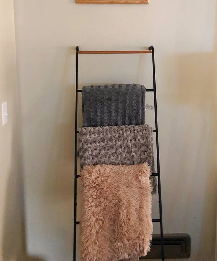 Reviewer pic of the leaning ladder in black against the wall with blankets hanging over it.