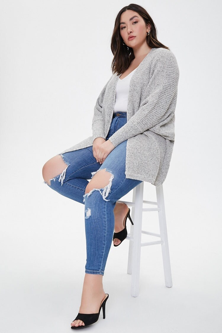 """A model wearing the cardigan in the """"cream/black"""" color"""