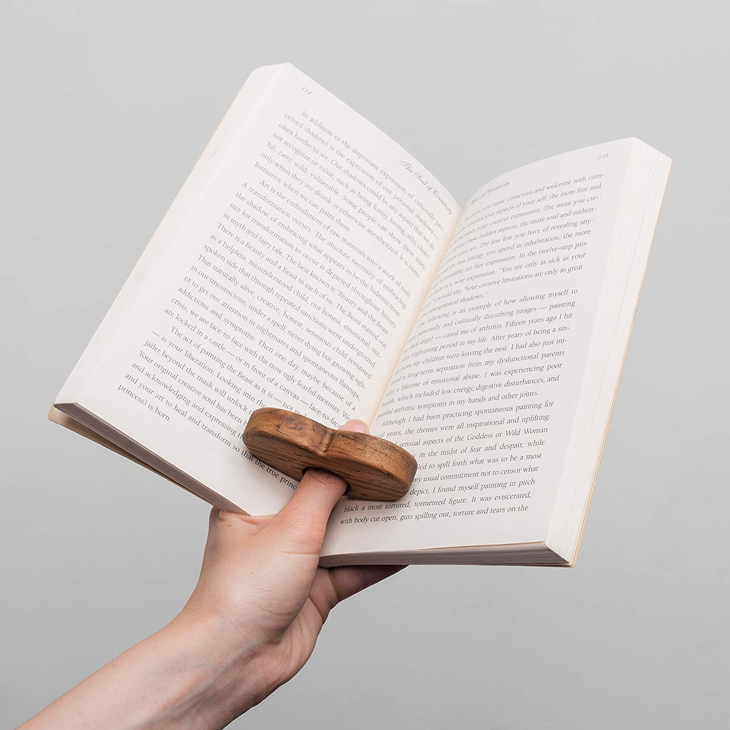 A person holds an book open while wearing the wooden book holder on their thumb