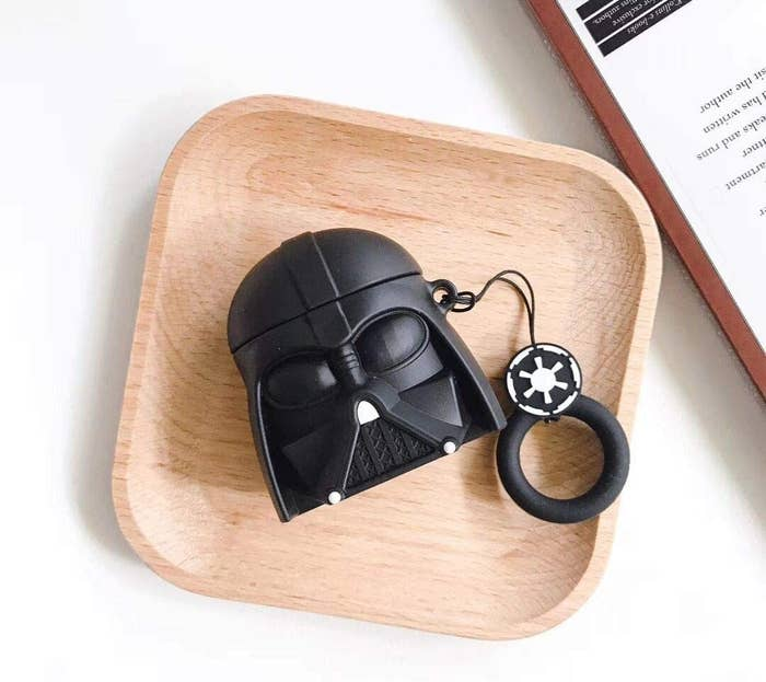 A top-down view of a Darth Vader AirPod case on a wooden tray