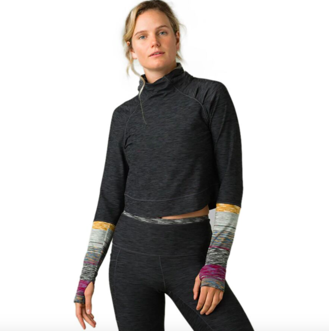 Model wears gray leggings and gray funnel neck sweatshirt top with multi-colored armholes