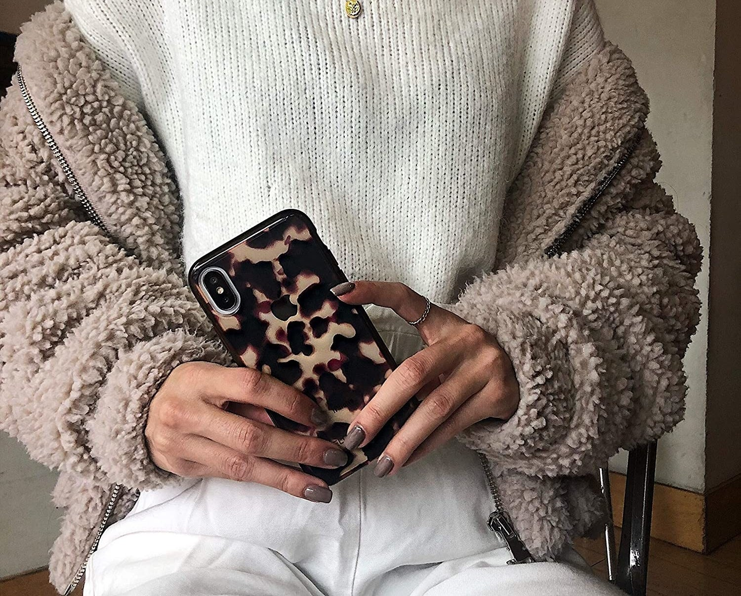 A person holds their phone in front of themselves