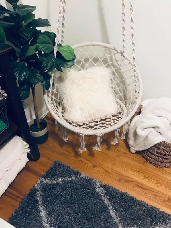 Reviewer pic of the circular macrame hammock chair hanging from the ceiling in the corner of the room.