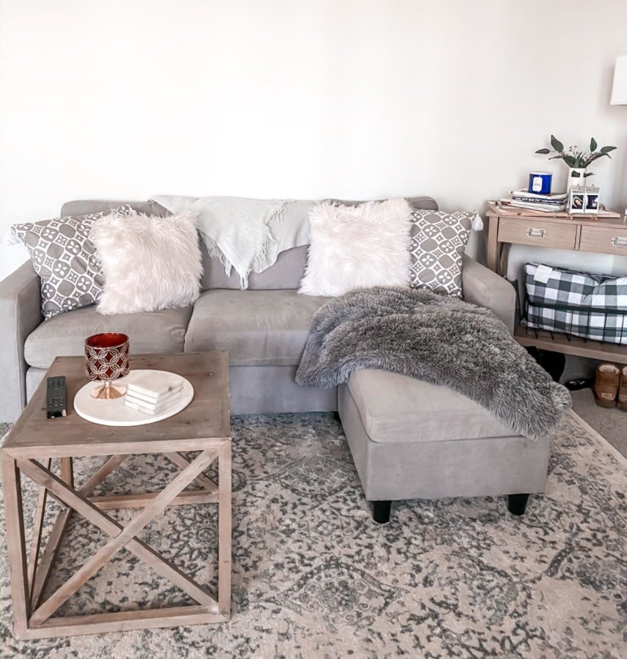 Reviewer pic of the couch in grey with an ottoman, making it into an l-shaped couch in a living room.