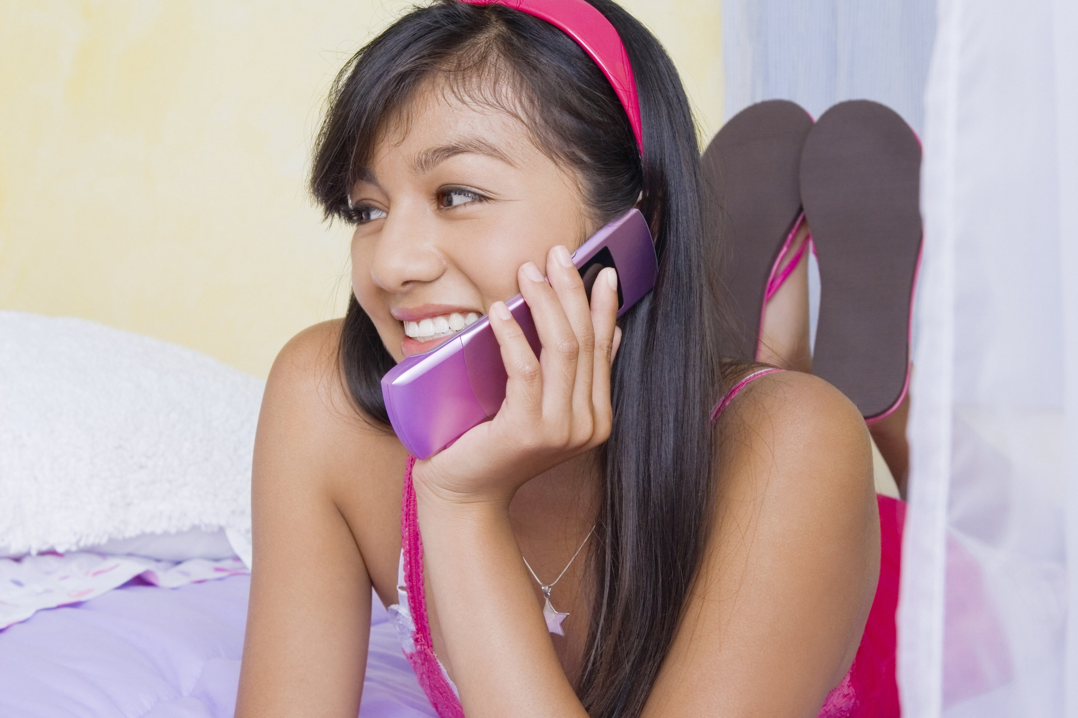 A a stock image of a teen girl laying on her bed talking on a hot pink flip phone