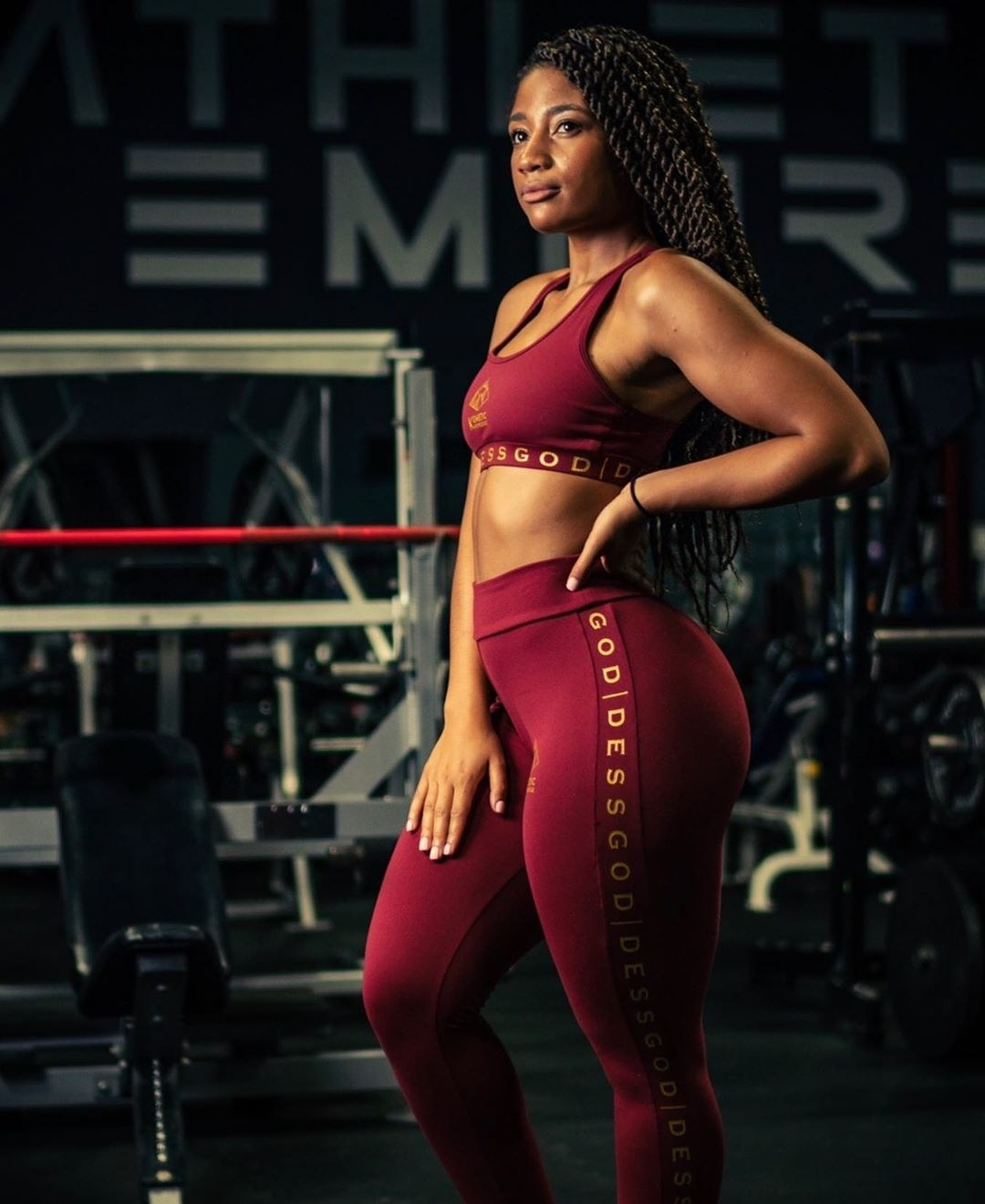 "Model wears red sports bra with gold lettering that says ""Kemetic Knowledge"""