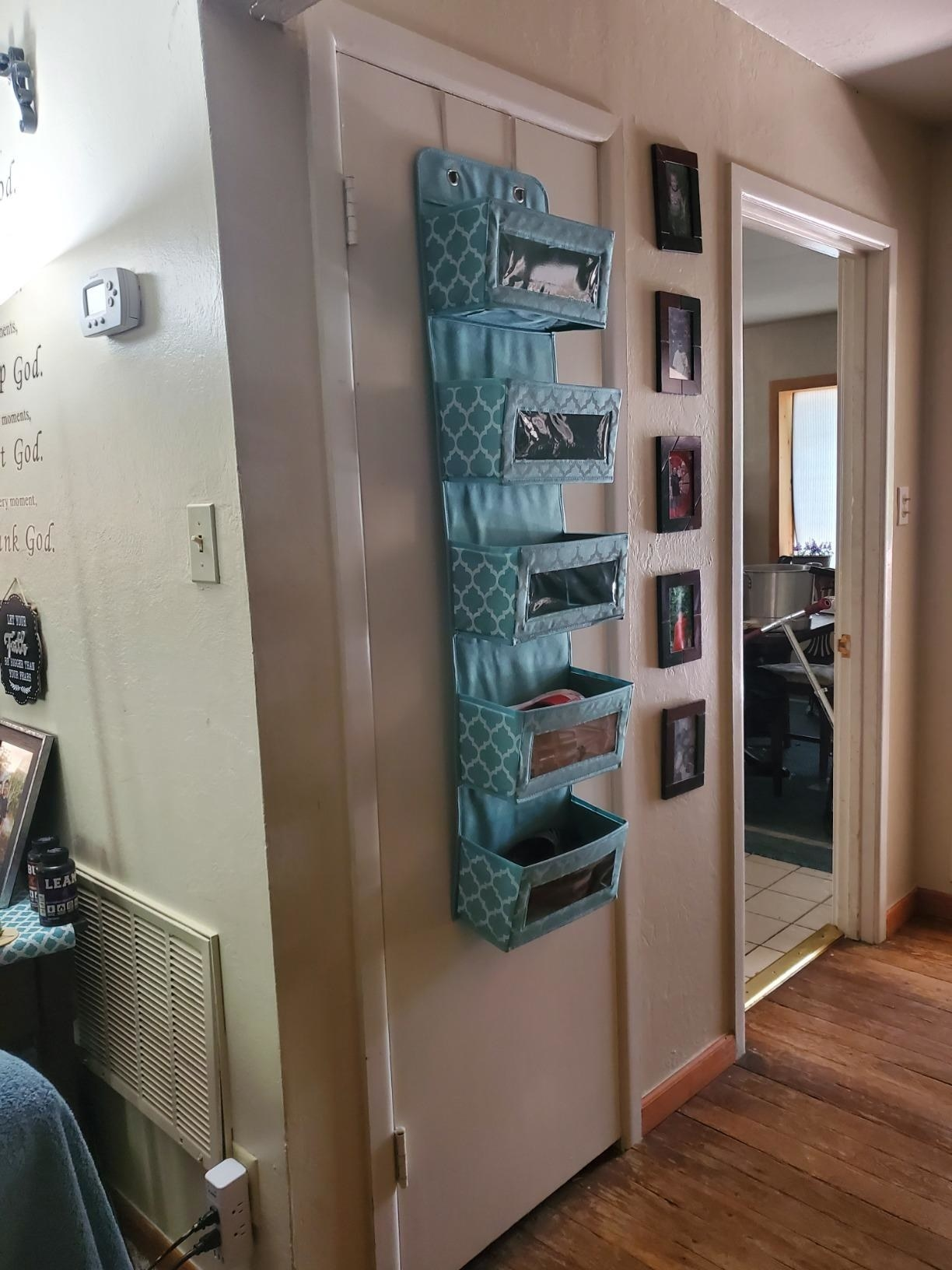 The blue Over The Door Hanging Organizer with 5 Large Clear Window Pockets hanging from a customer's closet door