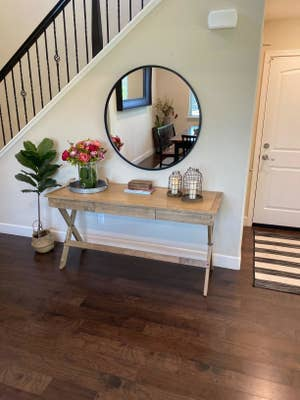 Reviewer pic of the round mirror with the black frame over a skinny table next to a staircase