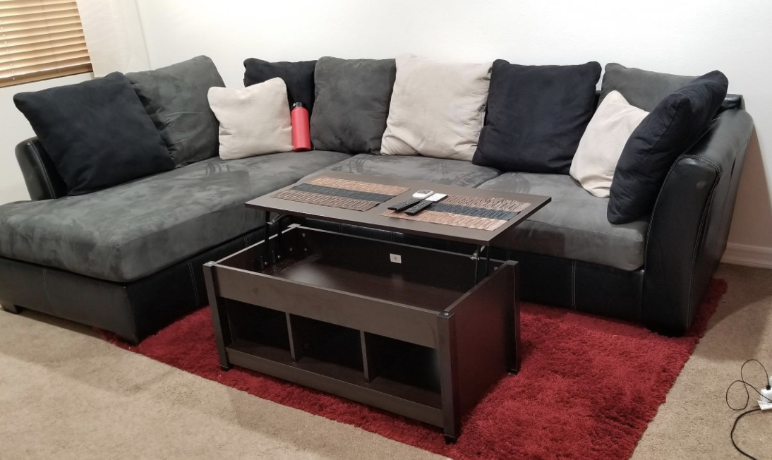 Reviewer photo fo the brown wood coffee table with the top lifted up in a living room in front of a big couch