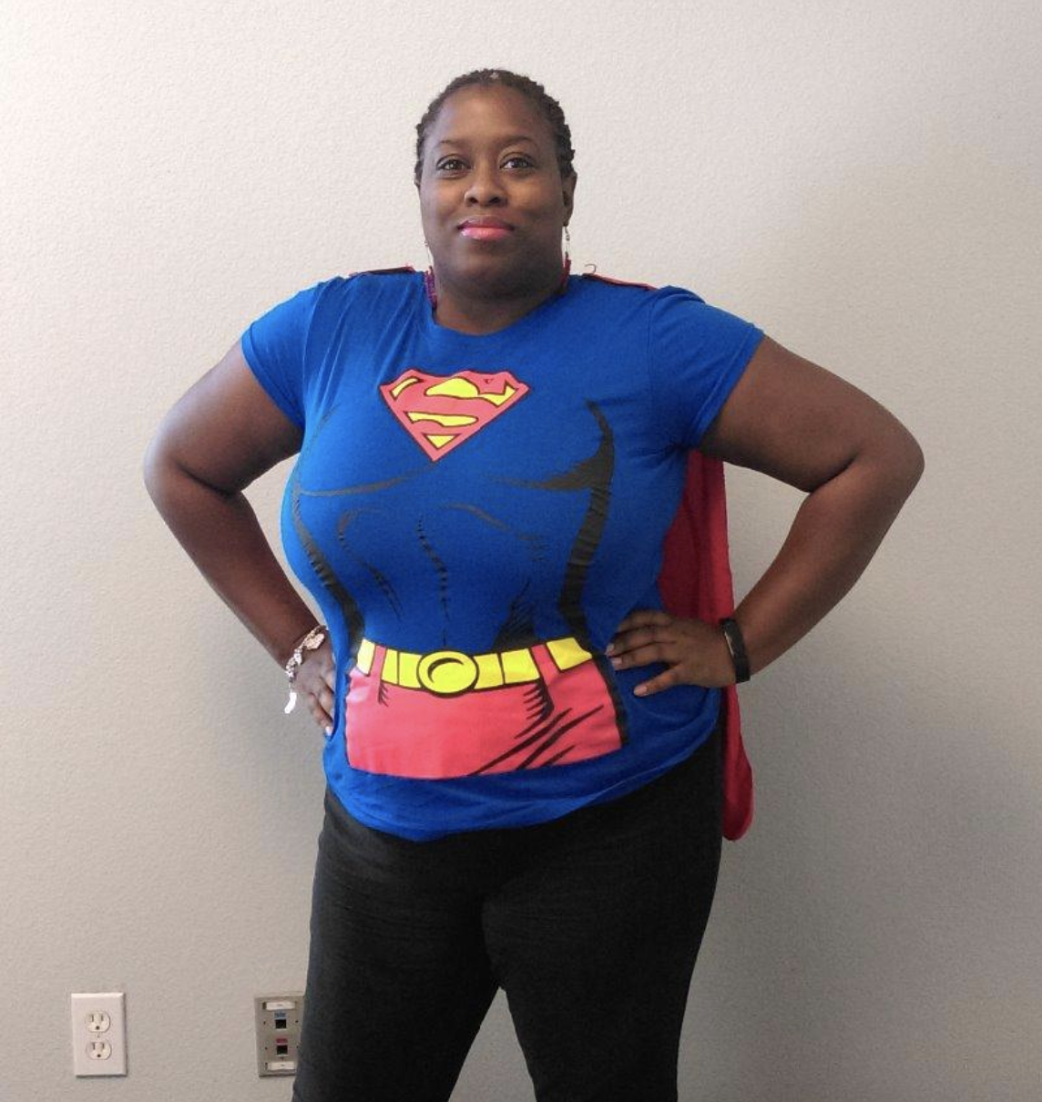 reviewer wearing blue and red tee with cape