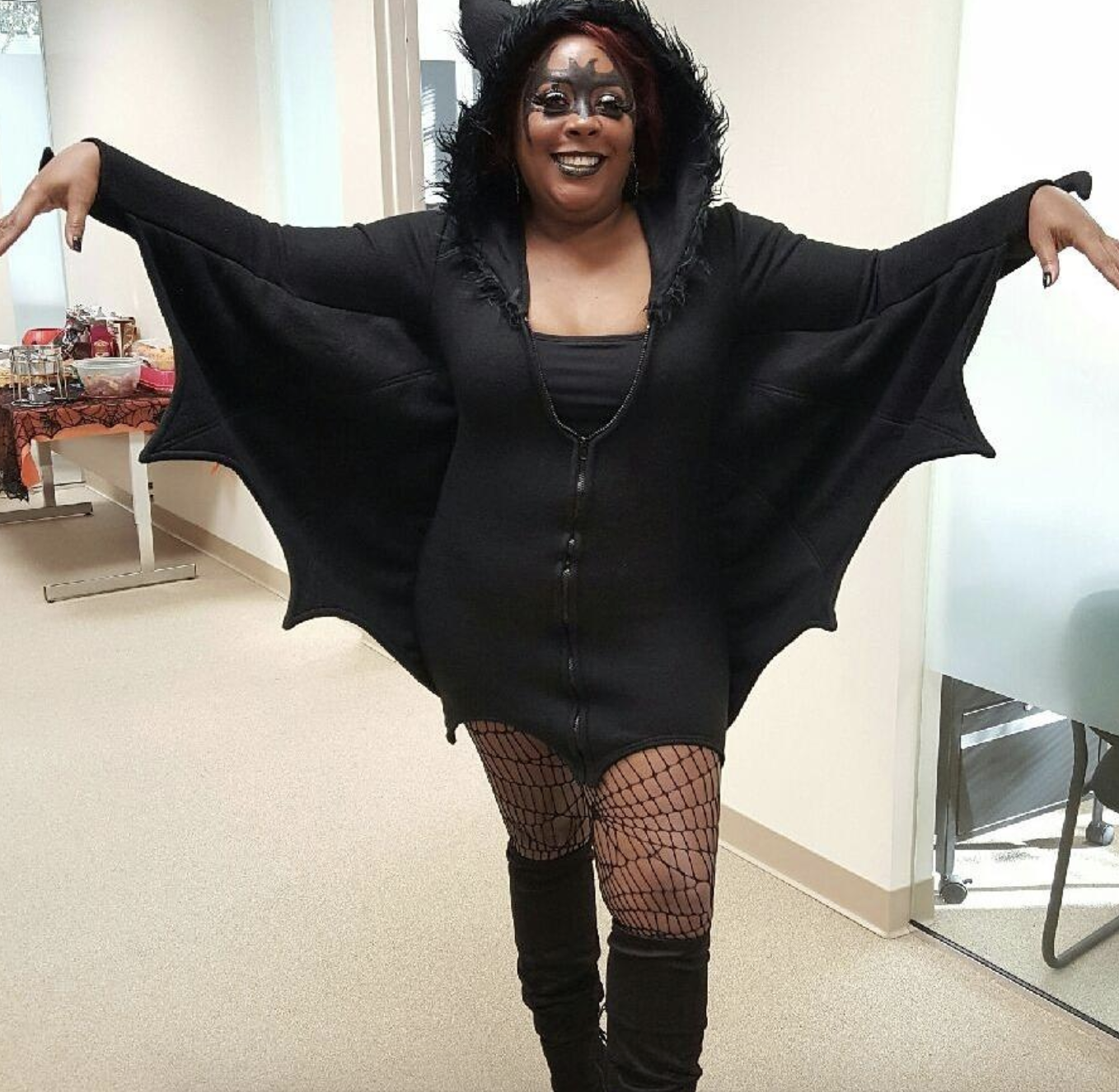 reviewer wearing the black bat-shaped sweater dress