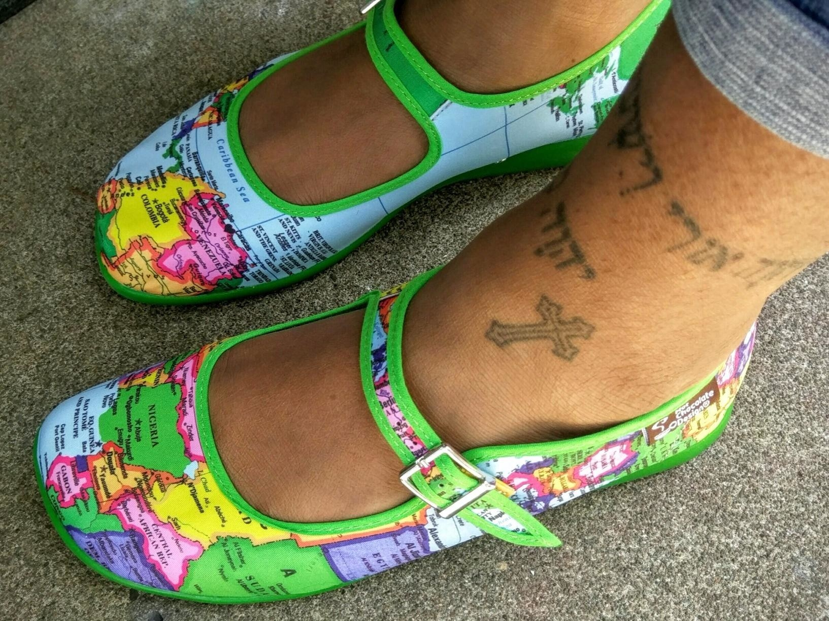 A reviewer wearing the green, blue, yellow, purple, and pink world map flats