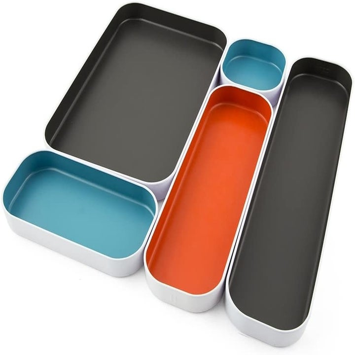 The different size trays in gray, orange, and blue