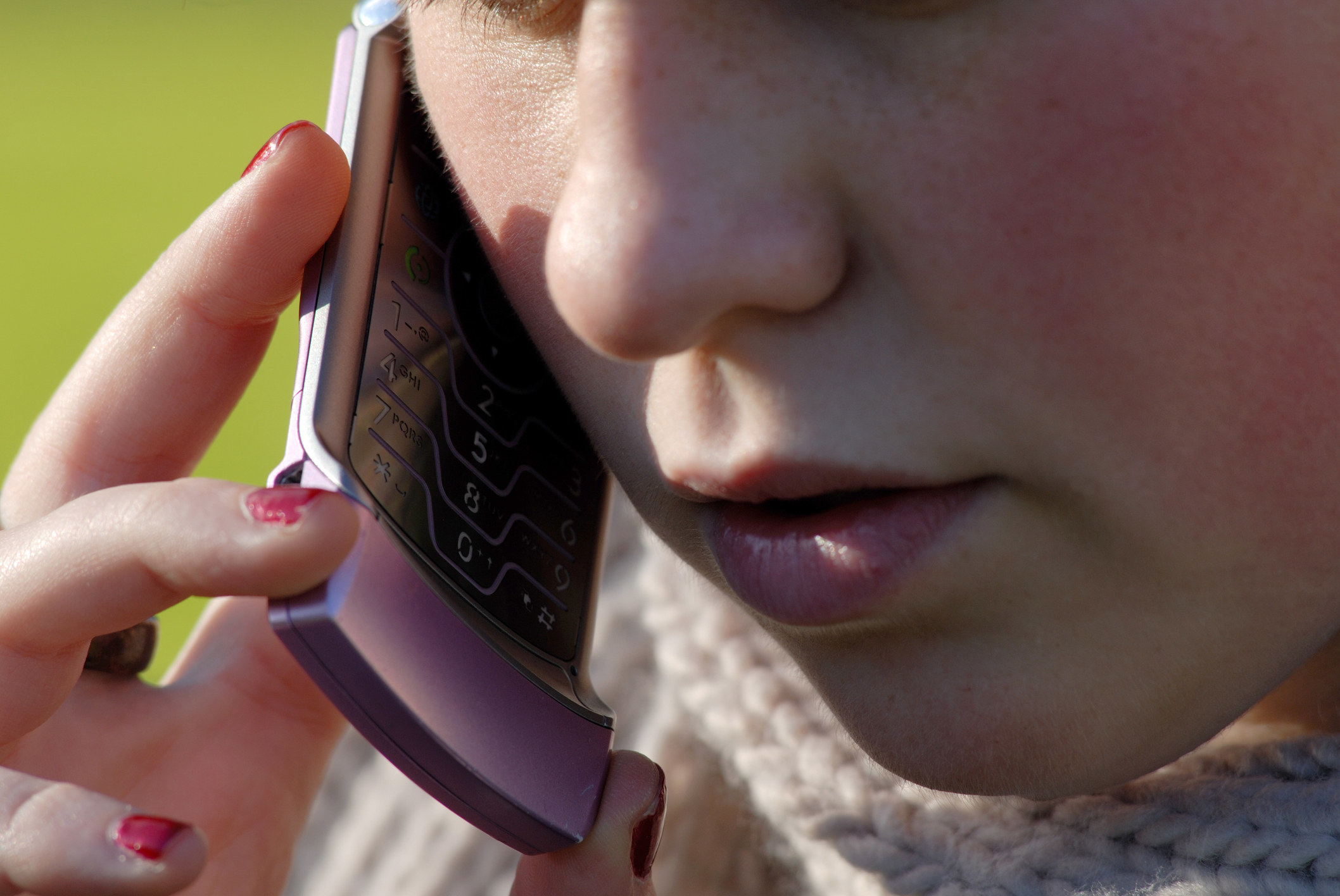 A stock image of a close-up of a teen girl talking on a hot pink Razr phone