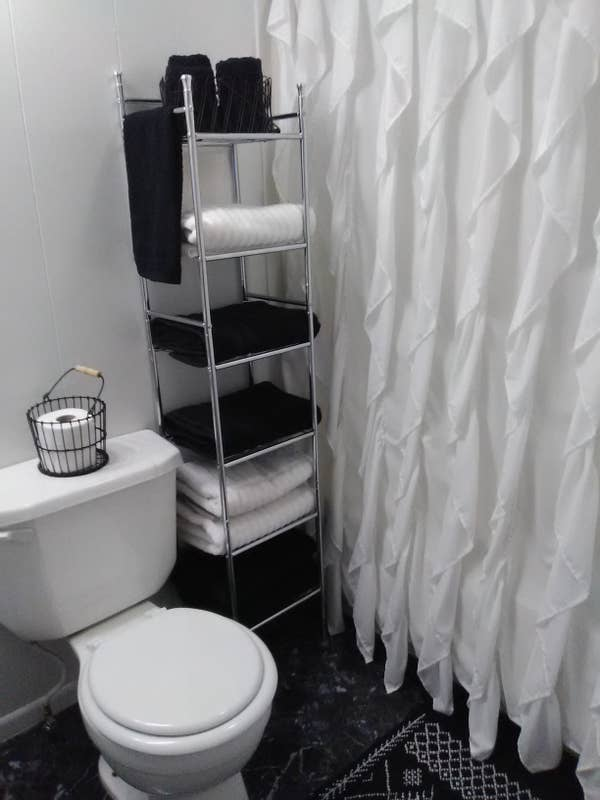 Reviewer pic of the six-shelf rack between a toilet and shower with towels on each shelf