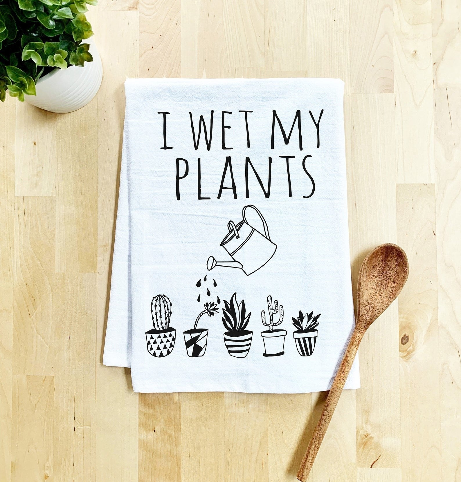 """White flour sack towel with black print of five small plants, a watering can, and the words """"I wet my plants"""""""