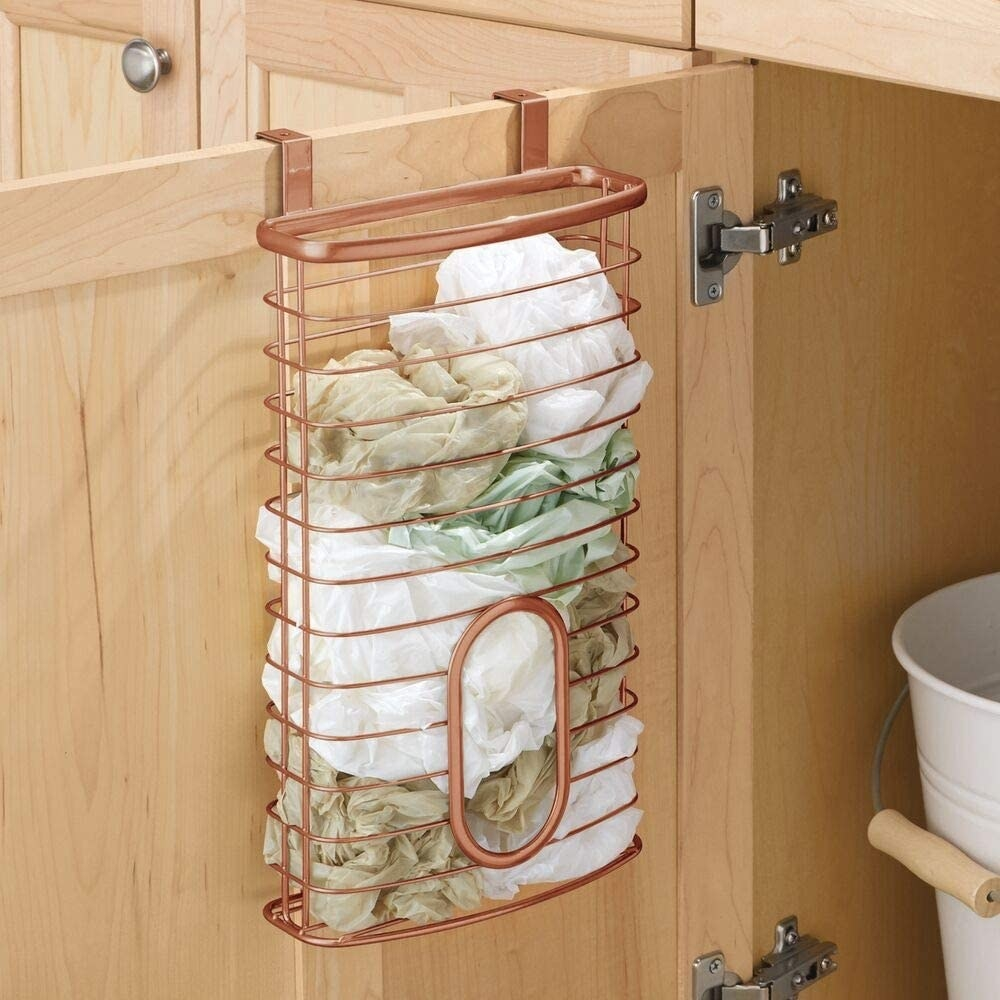 The copper plastic bag organizer hanging on a kitchen cabinet