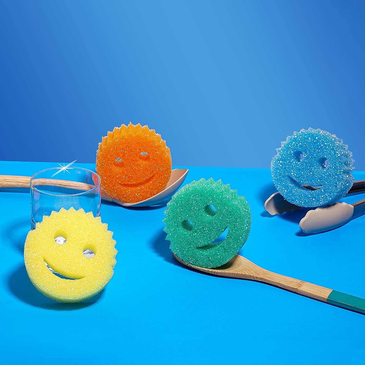 Four round, 1-inch thick smiley-faces sponges with two holes for eyes and a crescent-shaped hole for a mouth