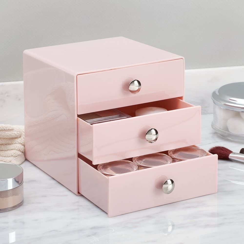 The blush pink iDesign Plastic 3-Drawer Jewelry Box on a counter, storing makeup