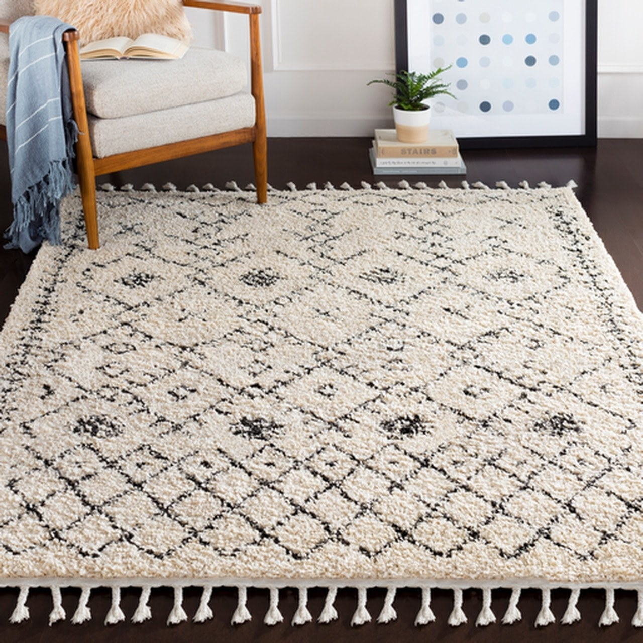 The rectangular rug with fringe on the end in white shag with a diamond pattern in black