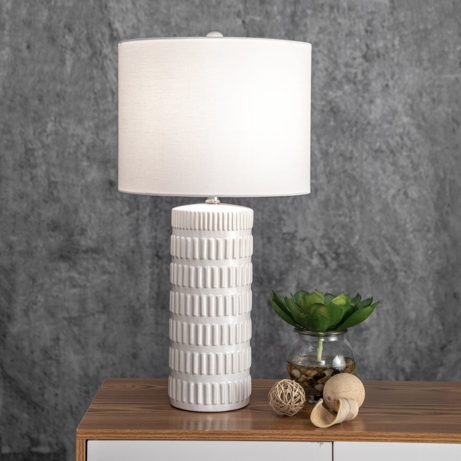 White tubular lamp with textured lines all over it and a white lampshade