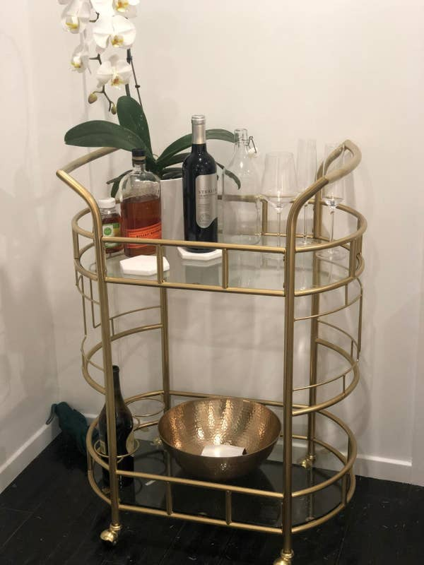 Reviewer pic of the oval-shaped bar cart in gold with assorted drinks and glasses on it