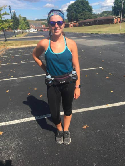 Reviewer wears black and purple hydration running belt with black capri leggings, a blue tank top, and gray running sneakers