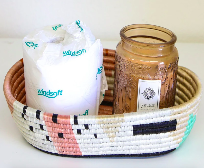The Pink Shapes Basket from Jungalow holding a roll of toilet paper and a candle