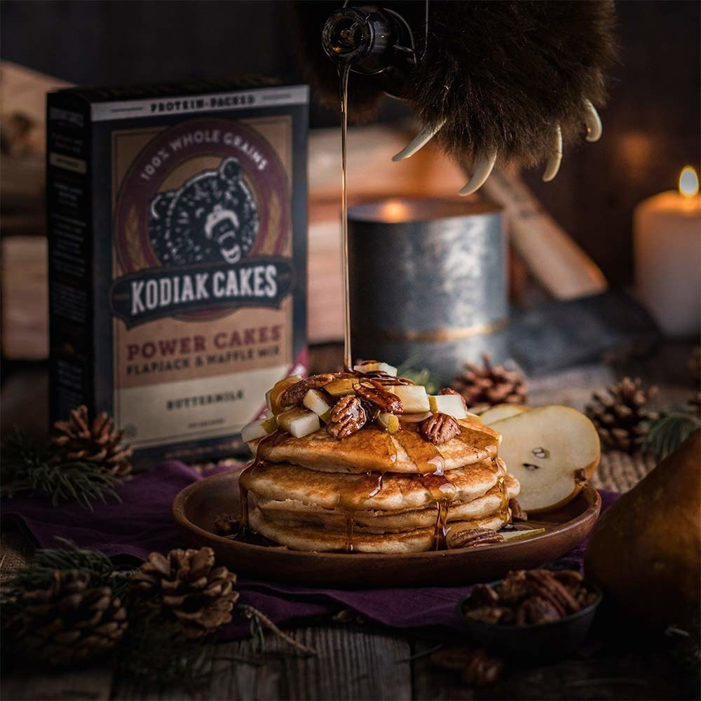 A bear paw pours syrup over a stack of the pancakes, with the Kodiak Power Cakes in the background