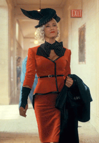 structured coat with sharp shoulders, fingerless gloves, and a V neckline with a striped collar, then a matching long pencil skirt and a large structured hat