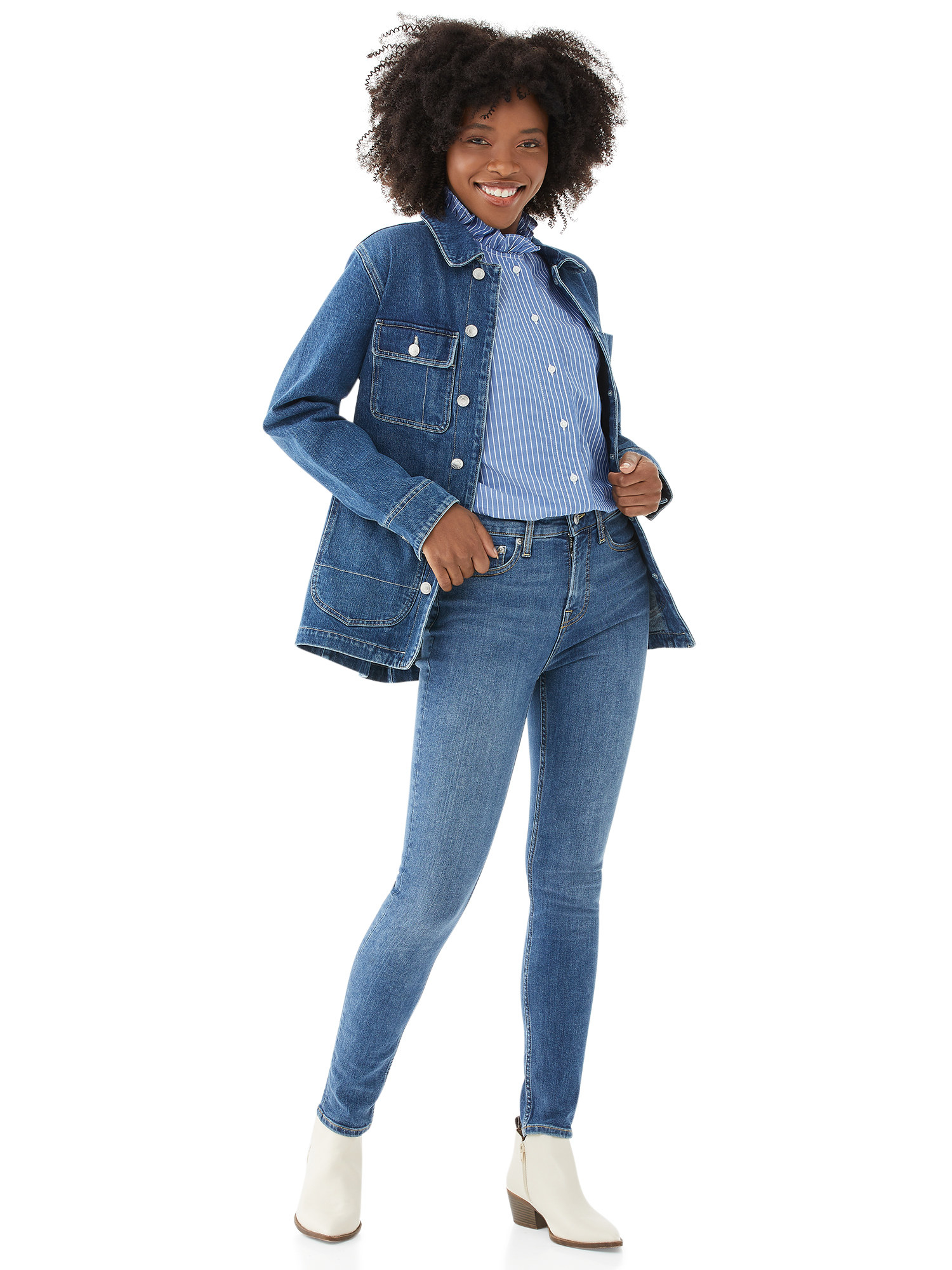 Model wears high rise skinny jeans with white booties and a denim jacket