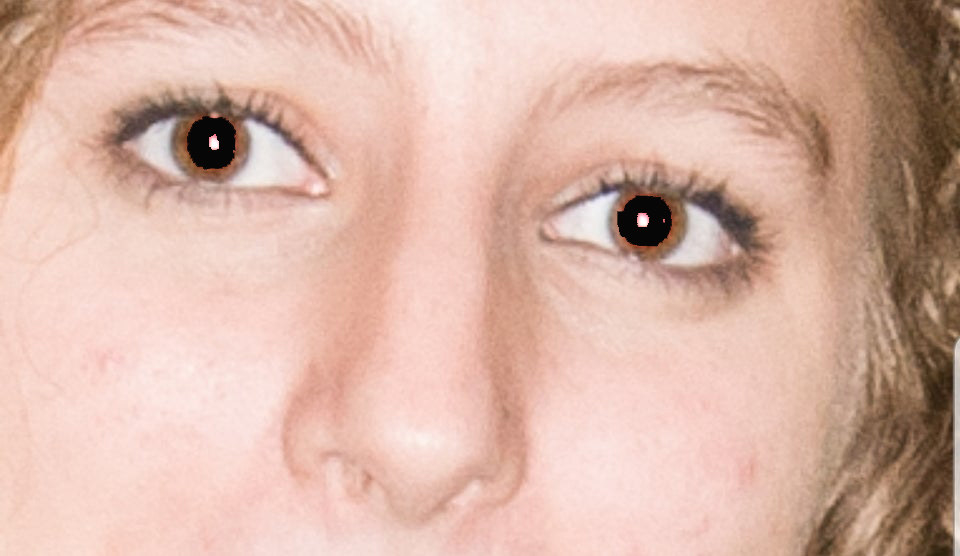 A close-up photo of eyes with the the red from the flash being covered by black with photo shop