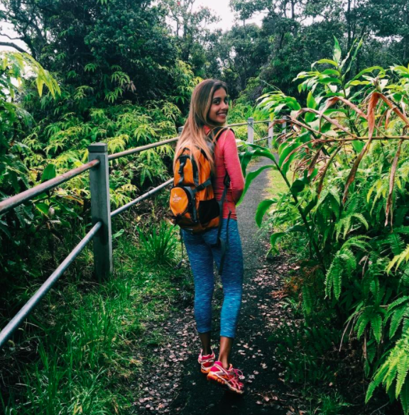 Reviewer wears orange hydration pack with blue leggings, a pink compression top, and pink sneakers while enjoying a hike in Hawaii