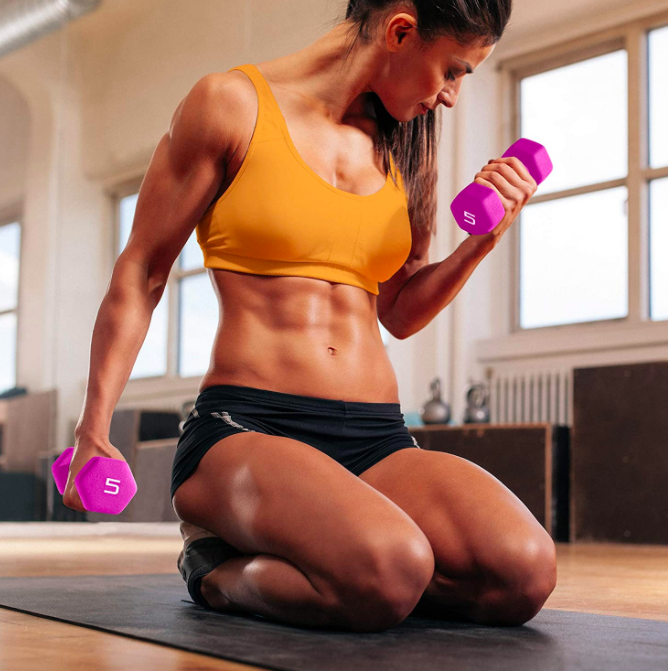 Model holds two pairs of pink five-pound neoprene dumbbells in their hands while working out on a mat