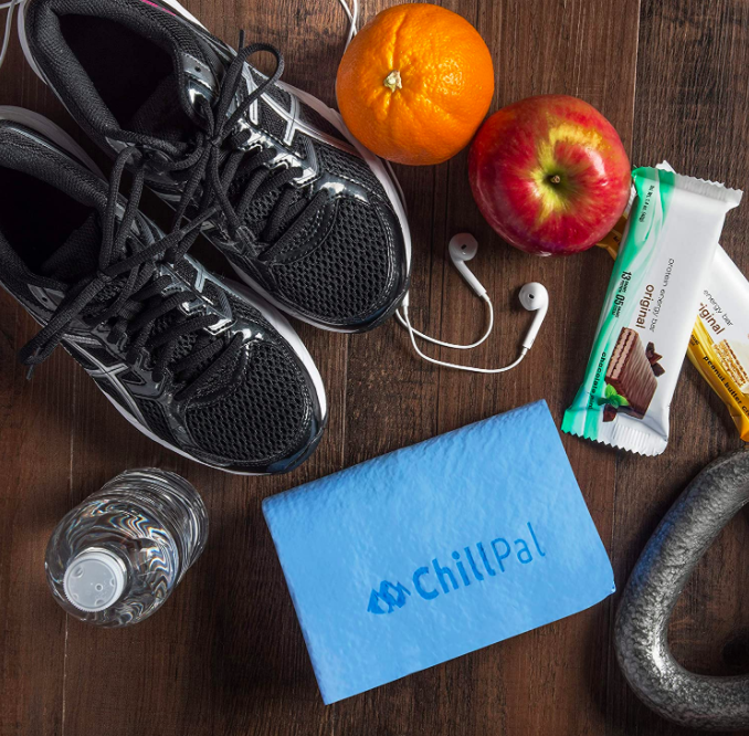 "Blue cooling towel that says ""ChillPal"" next to black workout sneakers and two protein bars on a table"