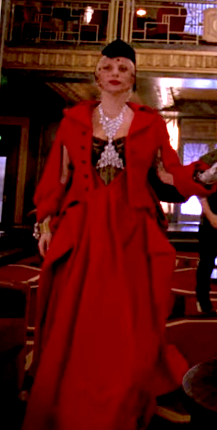 Long ballgown with folds down the sides, a matching conductor style structures unbuttoned jacket, a lace corset underneath, and a jeweled holster necklace that connects under the chest, with a hat with funeral hairnet