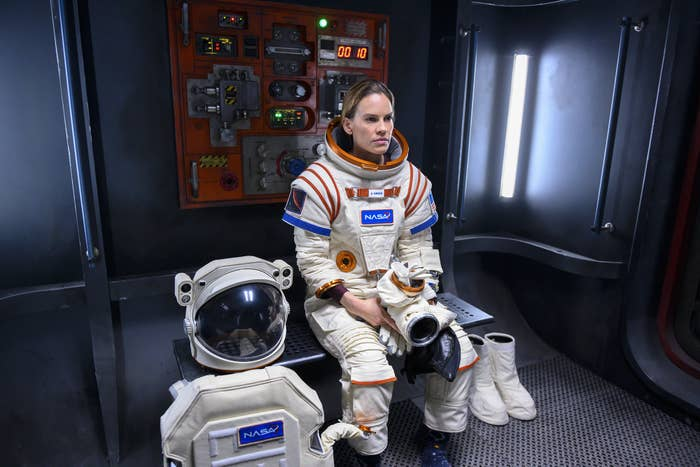 Hilary Swank sitting down with her space gear on, in the show Away