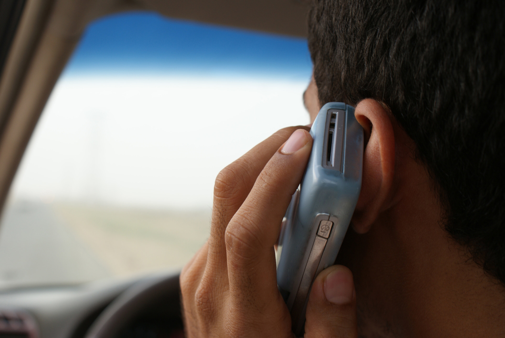 A stock image of a teen sitting in a car with phone up to his ear