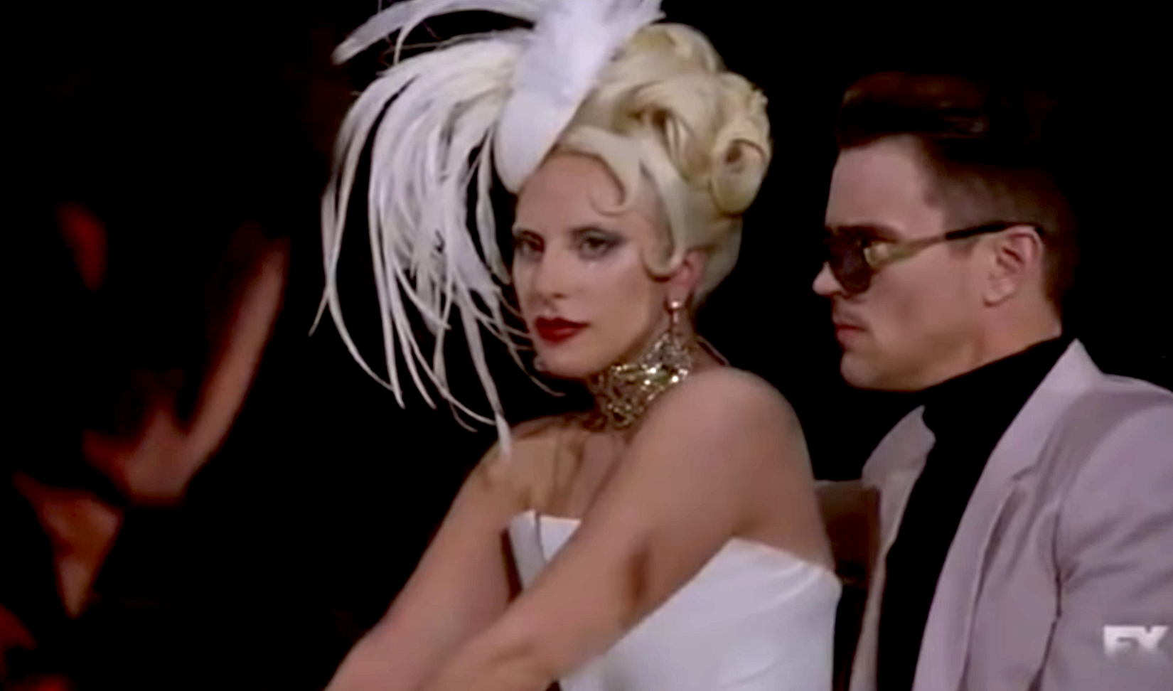 Lady Gaga in a structured strapless dress and white fat with long feathers coming out of it
