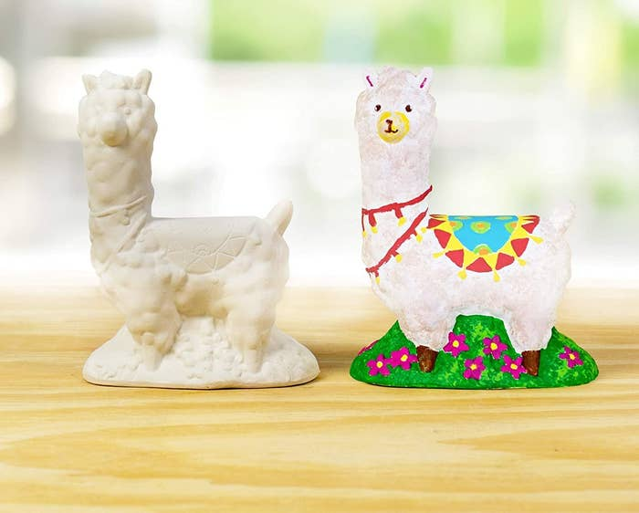 An unpainted ceramic llama beside a painted one