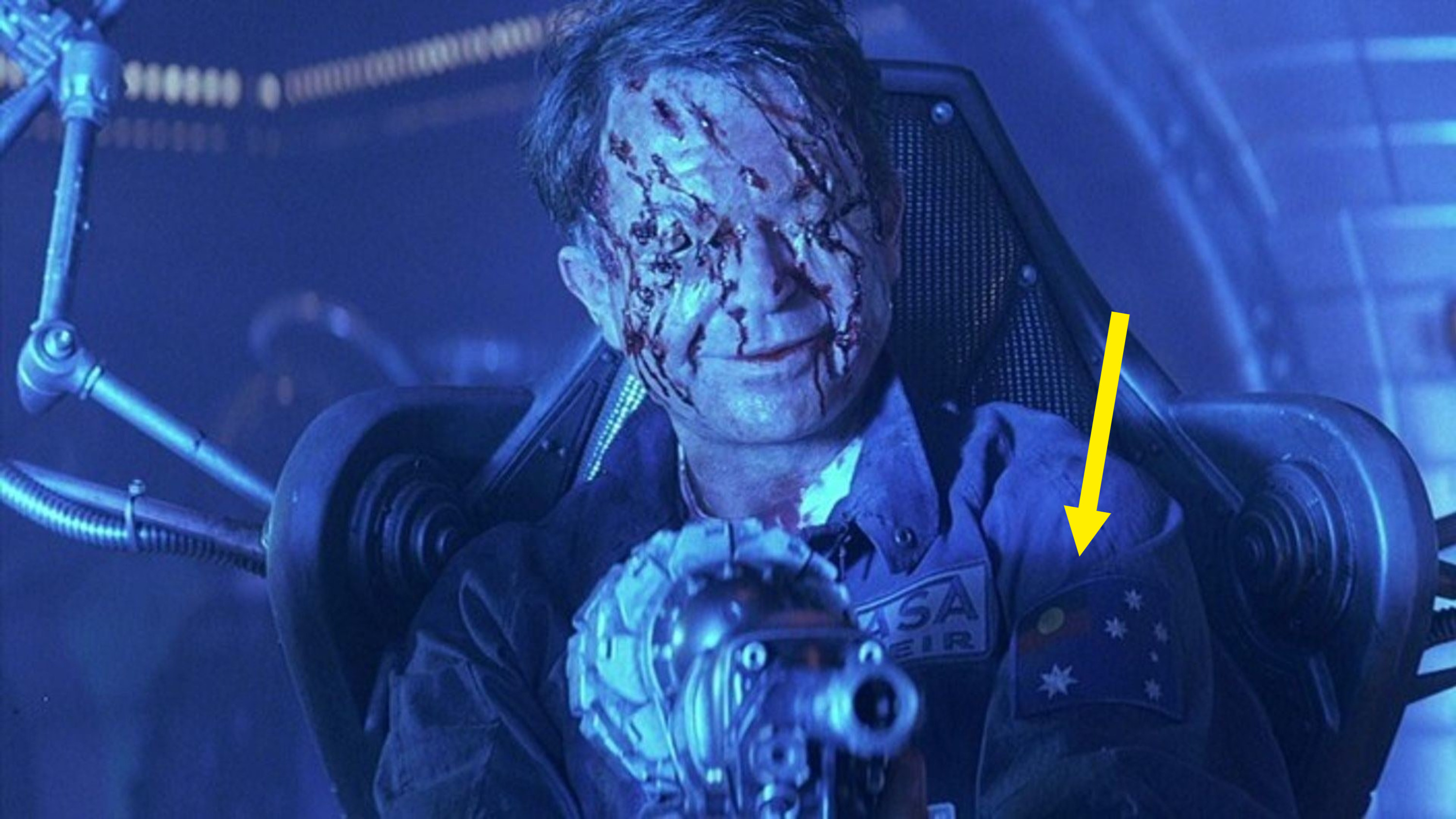 """Sam Neill's character in """"Event Horizon"""" holding a gun. You can see the Aboriginal flag on his uniform"""
